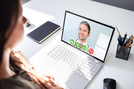 Photo pour Young Female Video Chatting With Doctor On Laptop - image libre de droit