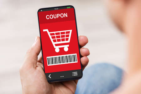 Photo pour Close-up Of Man's Hand Holding Mobile Phone With Shopping Coupon - image libre de droit