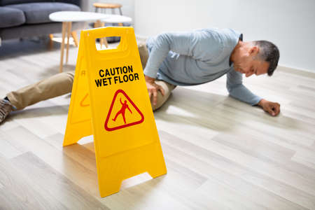 Photo for Mature Man Falling On Wet Floor In Front Of Caution Sign At Home - Royalty Free Image
