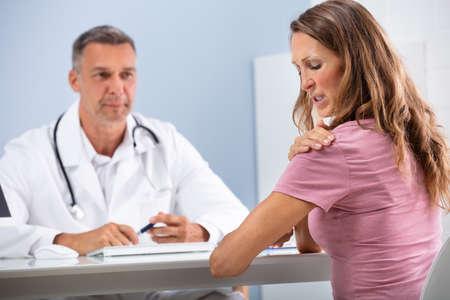 Photo pour Mature Doctor Looking At Female Patient Showing Her Paining Shoulder In Clinic - image libre de droit