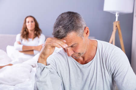 Photo for Close-up Of Depressed Man Sitting On Bed In Front Of Her Wife At Home - Royalty Free Image