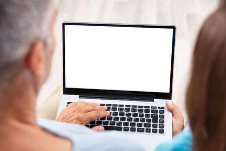 Photo pour Close-up Of A Couple Using Laptop At Home - image libre de droit