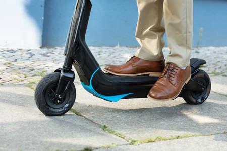 Photo pour Young Man Riding An Electric Kick Scooter - image libre de droit