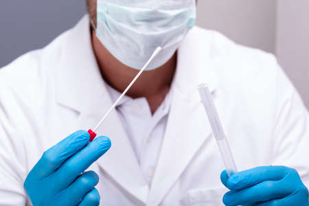 Photo pour Male Doctor Wearing Blue Gloves Holding Cotton Swab And DNA Test Tube - image libre de droit