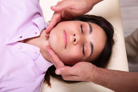 Photo pour Close-up Of A Relaxed Young Woman Receiving Jaw Massage From Physiotherapist In Clinic - image libre de droit
