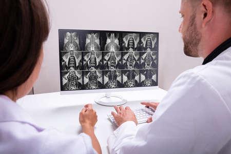 Foto de Doctors Looking At An MRI Scan At Computer In Clinic - Imagen libre de derechos