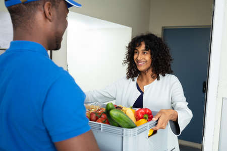 Photo for Smiling Woman Receiving Grocery Delivery At Home - Royalty Free Image