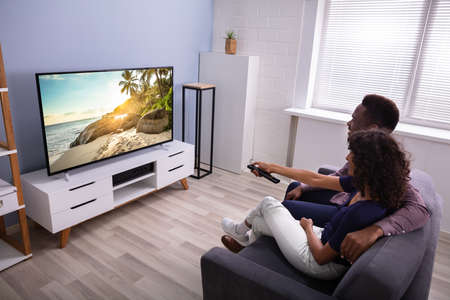 Photo pour Affectionate Young Family Watching TV At Home - image libre de droit