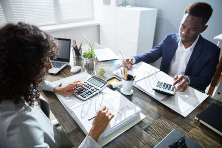 Photo pour Two Business Colleagues Calculating Tax In Office - image libre de droit