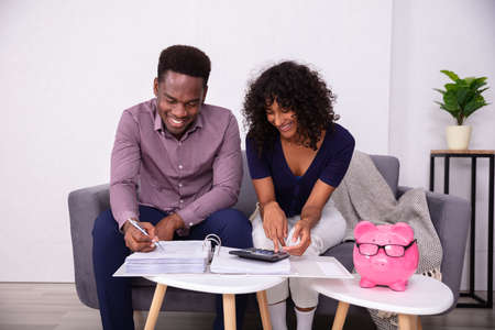 Photo pour Young Couple Sitting On Sofa Calculating Invoices At Home - image libre de droit