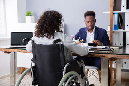 Photo for Businesswoman Sitting In Wheelchair Working In Office - Royalty Free Image