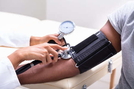 Photo pour Close-up Of Female Doctor's Hand Checking Blood Pressure - image libre de droit