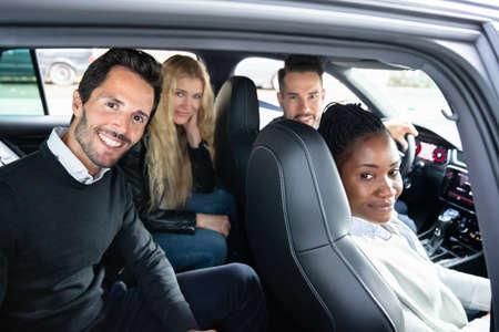 Photo pour Happy Portrait Of Smiling Multi Racial Friends Sitting Inside Car - image libre de droit