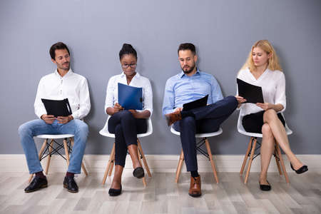 Photo pour Multiethnic Businesspeople Sitting On Chairs In Row Waiting For Job Interview Against Gray Wall - image libre de droit