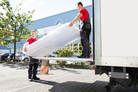 Photo pour Young Male Movers Unloading The Wrapped Mattress From Moving Truck - image libre de droit