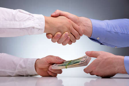 Photo pour Close-up Of Businessmen Sealing The Deal With Handshake And Receiving A Bribe Money - image libre de droit