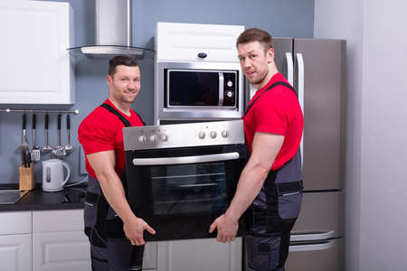 Photo for Side View Of Two Young Male Worker Placing Modern Oven Inside The Cabinet In Kitchen - Royalty Free Image