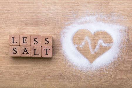 Photo pour Less Salt Near Heart Shape With Heartbeat On Wooden Desk - image libre de droit