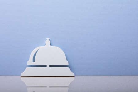 Photo pour Close-up Of A Concierge Bell Symbol Leaning On Blue Wall - image libre de droit