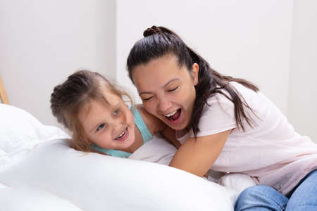 Photo pour Happy Mother And Her Daughter Child Girl Playing And Hugging On Bed - image libre de droit
