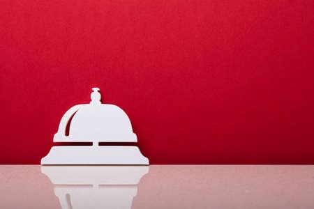 Photo pour Close-up Of A Concierge Bell Symbol Leaning On Red Wall - image libre de droit