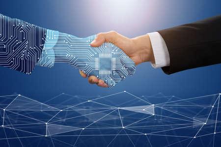 Photo pour Close-up Of Businessman Shaking Hand With Digital Partners Against Blue Technology Background - image libre de droit