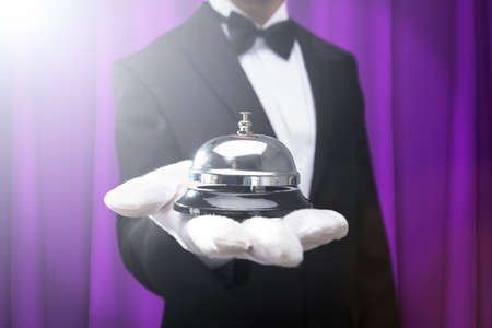 Photo pour Midsection Of Male Waiter Holding Service Bell On Hand Against Purple Curtain - image libre de droit