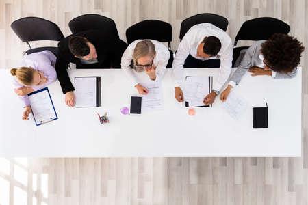 Photo pour Panel Of Corporate Personnel Officers Sitting At A Table - image libre de droit