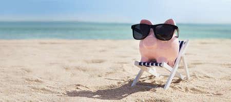 Photo pour Pink Piggybank Wearing Eyeglasses On Deck Chair Over The Sandy Beach - image libre de droit