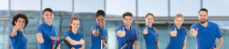 Photo pour Portrait Of A Smiling Diverse Young Janitors With Cleaning Equipment Against Window Glass - image libre de droit