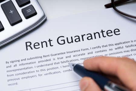 Photo pour Person Filling Rent Guarantee Form Holding Pen On Desk With Calculator And Spectacles - image libre de droit