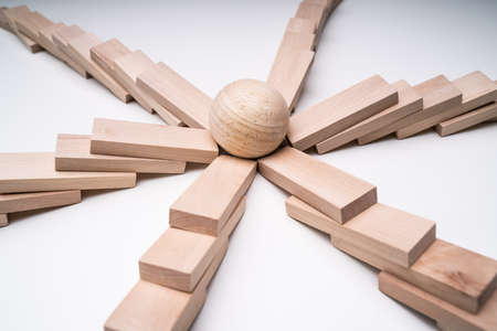 Foto de Close-up Of A Silver Ball In The Center Of Collapsed Wooden Dominoes Over White Backdrop - Imagen libre de derechos