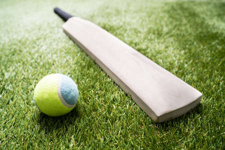 Foto de Close-up Of Wooden Cricket Bat And Ball On Turf Grass - Imagen libre de derechos