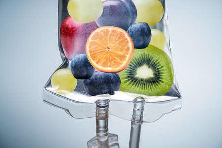 Photo pour Close-up Of A Different Fruit Slices Inside Saline Bag Hanging With Hook In Hospital - image libre de droit