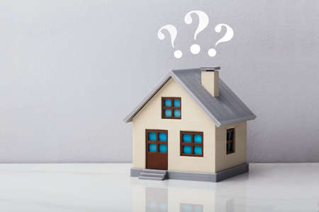 Photo pour Small House Model With Question Marks Over Reflective Desk Against Grey Background - image libre de droit