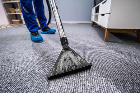 Foto de Close-up Of A Cleaning Carpet With Vacuum Cleaner - Imagen libre de derechos