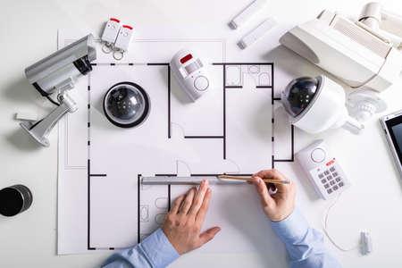 Photo pour Close-up Of An Architect's Hand Drawing Blueprint With Security Equipment On Desk - image libre de droit