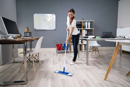 Photo pour Full Length Of Female Janitor Mopping Floor In Office - image libre de droit