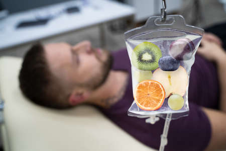 Photo pour Man In In Hospital Getting IV Infusion Of Fruit Slices Inside Saline Bag - image libre de droit
