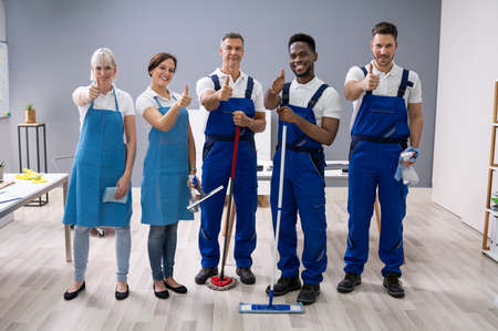 Photo pour Portrait Of Happy Diverse Janitors In The Office With Cleaning Equipment Showing Thumb Up Sign - image libre de droit