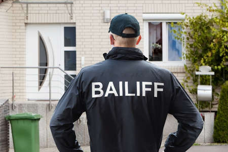Photo for Rear View Of A Male Bailiff Standing With His Hands On Hips At House Entrance - Royalty Free Image