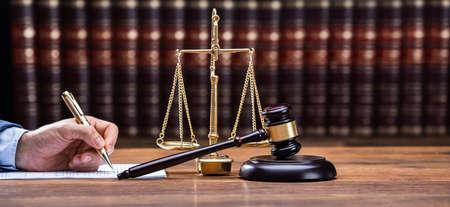 Photo pour Judge Writing On Legal Documents At Desk - image libre de droit