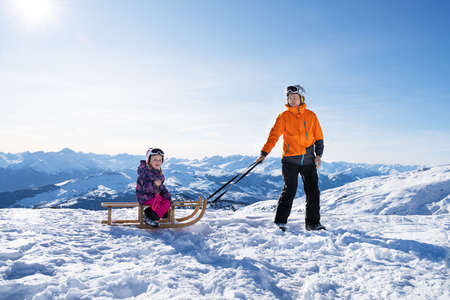 Photo for Young Man Looking At Camera While Pulling His Daughter On Wooden Sledge In Snow - Royalty Free Image