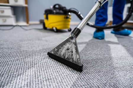 Photo pour Photo Of Janitor Cleaning Carpet With Vacuum Cleaner - image libre de droit