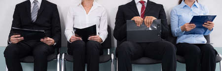 Photo pour Group Of Businesspeople With Files Sitting On Chair Waiting For Interview - image libre de droit