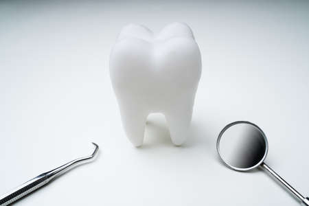 Photo pour Close-up Of Tooth With Dental Mirror Over White Background - image libre de droit