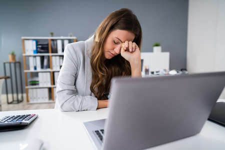 Photo for Sad Young Woman Working On Laptop At Desk - Royalty Free Image