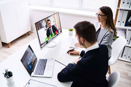 Photo pour Two Young Businesspeople Video Conferencing On Computer At Office - image libre de droit