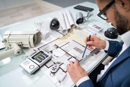 Photo pour Architect Drawing Blueprint With Various Security Equipment On Desk - image libre de droit