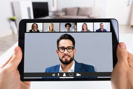 Photo pour Man Working From Home Online Group Videoconference On Tablet - image libre de droit